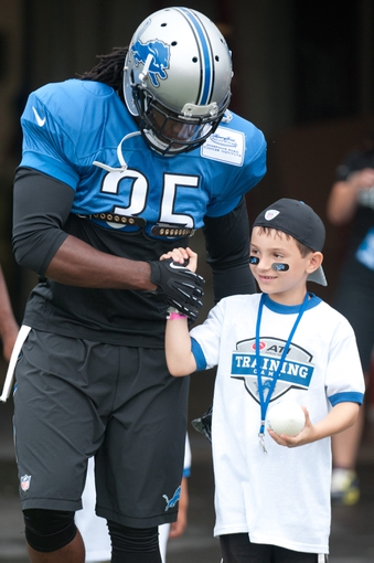 Aug 2, 2014; Detroit, MI, USA; Detroit Lions running back Joique Bell (35) and a young fan walk to the field during training camp at the Lions training facility. Mandatory Credit: Tim Fuller-USA TODAY Sports