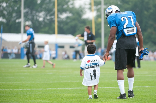 Aug 2, 2014; Detroit, MI, USA; Detroit Lions running back Reggie Bush (21) walks with a young fan to the field during training camp at the Lions training facility. Mandatory Credit: Tim Fuller-USA TODAY Sports