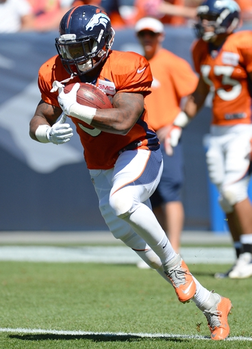 Aug 2, 2014; Denver, CO, USA; Denver Broncos running back Kapri Bibbs (35) runs with the football prior to the start of a scrimmage at Sports Authority Field. Mandatory Credit: Ron Chenoy-USA TODAY Sports