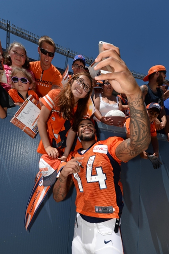 Aug 2, 2014; Denver, CO, USA; Denver Broncos wide receiver Cody Latimer (14) takes a photograph with fans following a scrimmage at Sports Authority Field. Mandatory Credit: Ron Chenoy-USA TODAY Sports
