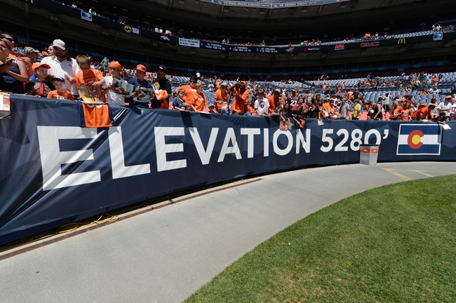 Aug 2, 2014; Denver, CO, USA; Denver Broncos fans await players for autographs on top of a elevation warning signage following a scrimmage at Sports Authority Field. Mandatory Credit: Ron Chenoy-USA TODAY Sports