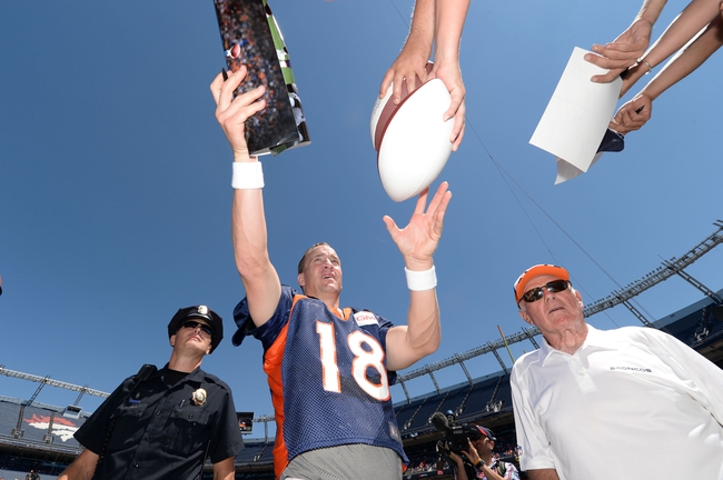 Aug 2, 2014; Denver, CO, USA; Denver Broncos quarterback Peyton Manning (18) signs autographs following a scrimmage at Sports Authority Field. Mandatory Credit: Ron Chenoy-USA TODAY Sports