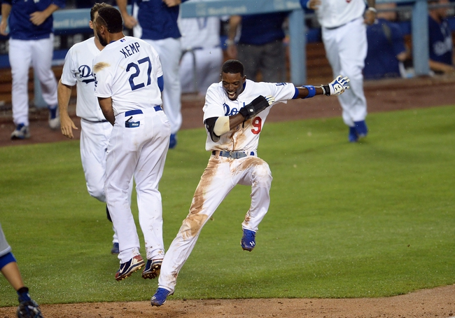 Aug 2, 2014; Los Angeles, CA, USA;  Los Angeles Dodgers second baseman Dee Gordon (9) is met by right fielder Matt Kemp (27) as he comes in to score on a 3-run walk off home run in the twelfth inning of the game by shortstop Hanley Ramirez (not pictured) to defeat the Chicago Cubs at Dodger Stadium. Dodgers won 5-2. Mandatory Credit: Jayne Kamin-Oncea-USA TODAY Sports