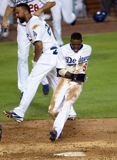 Aug 2, 2014; Los Angeles, CA, USA;  Los Angeles Dodgers second baseman Dee Gordon (9) is met by right fielder Matt Kemp (27) as he comes in to score on 3-run walk off home run in the twelfth inning of the game by shortstop Hanley Ramirez (13) to defeat the Chicago Cubs at Dodger Stadium. Dodgers won 5-2. Mandatory Credit: Jayne Kamin-Oncea-USA TODAY Sports