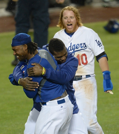 Aug 2, 2014; Los Angeles, CA, USA;  Los Angeles Dodgers center fielder Yasiel Puig (middle) and third baseman Justin Turner (10) celebrate with shortstop Hanley Ramirez (left) after Ramirez hit a walk off 3-run home run in the twelfth inning of the game against the Chicago Cubs at Dodger Stadium. Dodgers won 5-2. Mandatory Credit: Jayne Kamin-Oncea-USA TODAY Sports