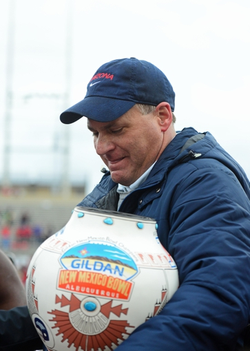 Dec. 15, 2012; Albuquerque, NM, USA; Arizona Wildcats head coach Rich Rodriguez celebrates with the trophy against the Nevada Wolf Pack in the 2012 New Mexico Bowl at University Stadium. Mandatory Credit: Mark J. Rebilas-USA TODAY Sports
