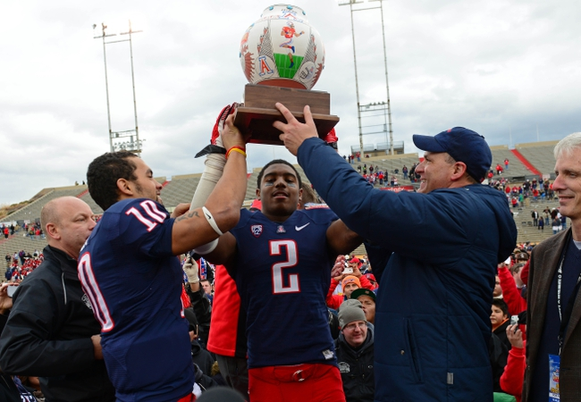 Dec. 15, 2012; Albuquerque, NM, USA; Arizona Wildcats quarterback Matt Scott (left), linebacker Marquis Flowers (center) and head coach Rich Rodriguez celebrate with the trophy following the game against the Nevada Wolf Pack in the 2012 New Mexico Bowl at University Stadium. Mandatory Credit: Mark J. Rebilas-USA TODAY Sports
