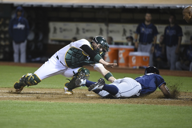 August 4, 2014; Oakland, CA, USA; Oakland Athletics catcher Derek Norris (36, right) tags out Tampa Bay Rays second baseman Sean Rodriguez (1, left) on a squeeze play during the ninth inning at O.co Coliseum. The Athletics defeated the Rays 3-2. Mandatory Credit: Kyle Terada-USA TODAY Sports
