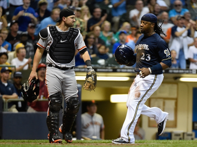 Aug 5, 2014; Milwaukee, WI, USA; Milwaukee Brewers second baseman Rickie Weeks (23) scores in front of San Francisco Giants catcher Andrew Susac (34) on a squeeze bunt by center fielder Carlos Gomez (not pictured) in the fifth inning at Miller Park. Mandatory Credit: Benny Sieu-USA TODAY Sports