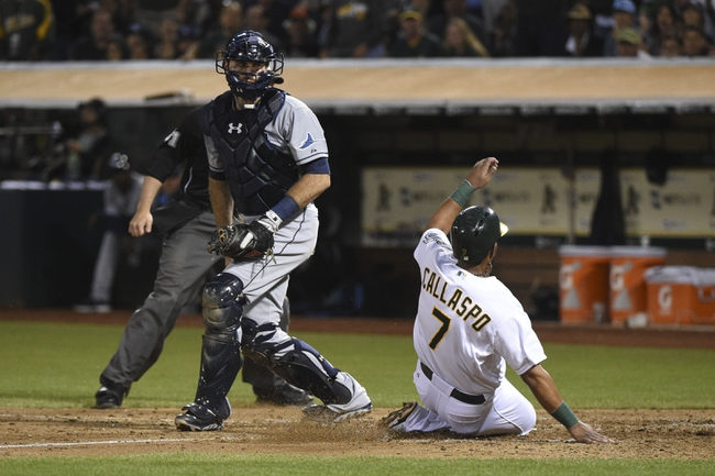 August 5, 2014; Oakland, CA, USA; Oakland Athletics second baseman Alberto Callaspo (7) scores on a RBI-single by designated hitter Coco Crisp (4, not pictured) against Tampa Bay Rays catcher Curt Casali (59, left) during the fifth inning at O.co Coliseum. Mandatory Credit: Kyle Terada-USA TODAY Sports