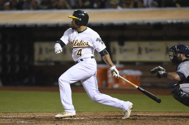 August 5, 2014; Oakland, CA, USA; Oakland Athletics designated hitter Coco Crisp (4) hits a RBI-single scoring second baseman Alberto Callaspo (7, not pictured) against the Tampa Bay Rays during the fifth inning at O.co Coliseum. Mandatory Credit: Kyle Terada-USA TODAY Sports