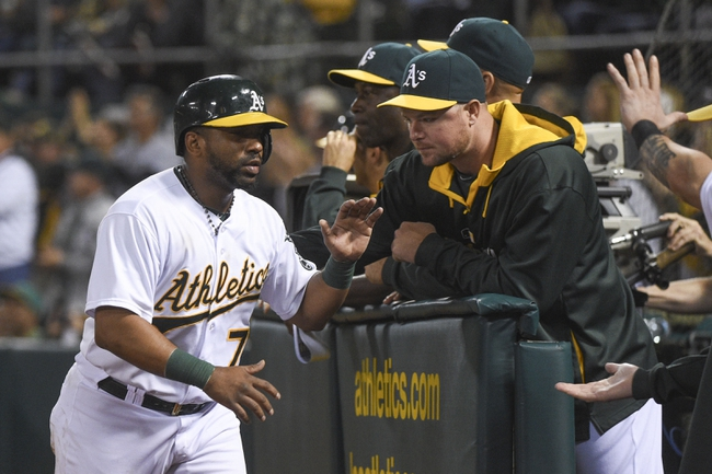 August 5, 2014; Oakland, CA, USA; Oakland Athletics second baseman Alberto Callaspo (7, left) is congratulated for scoring on a RBI-single by designated hitter Coco Crisp (4, not pictured) against the Tampa Bay Rays during the fifth inning at O.co Coliseum. Mandatory Credit: Kyle Terada-USA TODAY Sports
