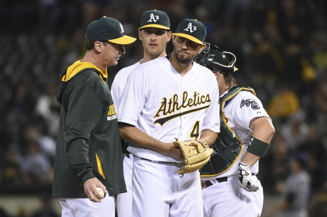 August 5, 2014; Oakland, CA, USA; Oakland Athletics starting pitcher Jason Hammel (40, front) is removed from the game by manager Bob Melvin (6, far left) against the Tampa Bay Rays during the sixth inning at O.co Coliseum. Mandatory Credit: Kyle Terada-USA TODAY Sports