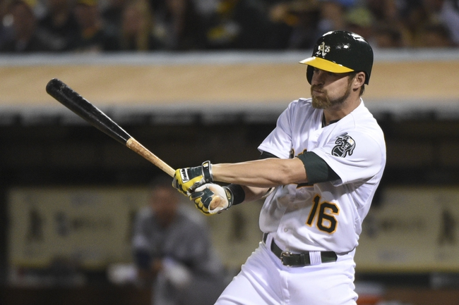 August 5, 2014; Oakland, CA, USA; Oakland Athletics right fielder Josh Reddick (16) hits a RBI-single scoring first baseman Nate Freiman (35, not pictured) against the Tampa Bay Rays during the sixth inning at O.co Coliseum. Mandatory Credit: Kyle Terada-USA TODAY Sports