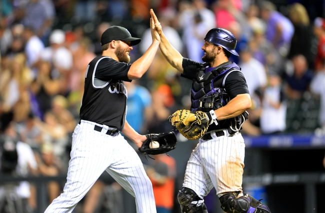 Aug 6, 2014; Denver, CO, USA; Colorado Rockies catcher Michael McKenry (8) and relief pitcher Brooks Brown (51) celebrate the win over the Chicago Cubs at Coors Field. The Rockies defeated the Cubs 13-4. Mandatory Credit: Ron Chenoy-USA TODAY Sports