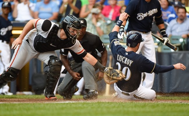 Aug 7, 2014; Milwaukee, WI, USA; Milwaukee Brewers catcher Jonathan Lucroy (20) scores on a double by right fielder Ryan Braun (not pictured) before the tag by San Francisco Giants catcher Andrew Susac (34) in the first inning at Miller Park. Mandatory Credit: Benny Sieu-USA TODAY Sports