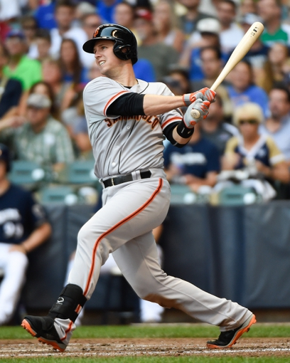 Aug 7, 2014; Milwaukee, WI, USA;  San Francisco Giants catcher Buster Posey (28) hits a single in the third inning against the Milwaukee Brewers at Miller Park. Mandatory Credit: Benny Sieu-USA TODAY Sports