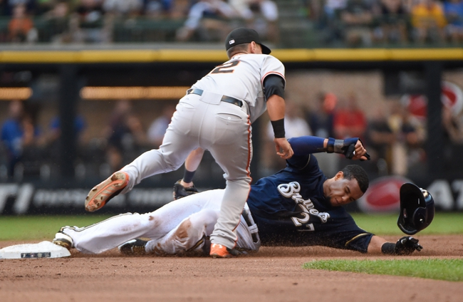 Aug 7, 2014; Milwaukee, WI, USA;  San Francisco Giants second baseman Joe Panik (12) tags out Milwaukee Brewers center fielder Carlos Gomez (27) trying to steal 2nd base in the first inning at Miller Park. Mandatory Credit: Benny Sieu-USA TODAY Sports