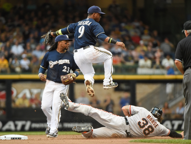 Aug 7, 2014; Milwaukee, WI, USA;  Milwaukee Brewers shortstop Jean Segura (9) jumps over San Francisco Giants left fielder Michael Morse (38) to complete a double play in the fourth inning at Miller Park. Mandatory Credit: Benny Sieu-USA TODAY Sports