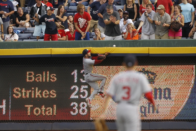 Aug 8, 2014; Atlanta, GA, USA; Washington Nationals right fielder Steven Souza (21) collides with the outfield wall as he attempts to catch a home run hit by Atlanta Braves first baseman Freddie Freeman (not pictured) in the second inning at Turner Field. Mandatory Credit: Brett Davis-USA TODAY Sports