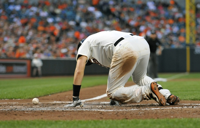 Aug 8, 2014; Baltimore, MD, USA; Baltimore Orioles second baseman Ryan Flaherty (3) goes down after being hit by a pitch in the third inning against the St. Louis Cardinals at Oriole Park at Camden Yards. Mandatory Credit: Joy R. Absalon-USA TODAY Sports