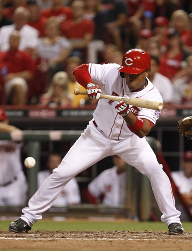 Aug 8, 2014; Cincinnati, OH, USA; Cincinnati Reds third baseman Ramon Santiago (7) bunts during the ninth inning against the Miami Marlins at Great American Ball Park. The Marlins won 2-1. Mandatory Credit: Frank Victores-USA TODAY Sports