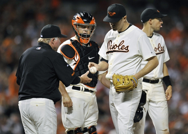 Aug 8, 2014; Baltimore, MD, USA; Baltimore Orioles manager Buck Showalter (26) takes the ball from starting pitcher Chris Tillman (30) in the seventh inning against the St. Louis Cardinals at Oriole Park at Camden Yards. The Orioles won 12-2. Mandatory Credit: Joy R. Absalon-USA TODAY Sports