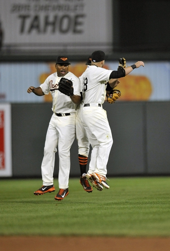 Aug 8, 2014; Baltimore, MD, USA; Baltimore Orioles outfielders Delmon Young (L), Steve Pearce (R), and David Lough (back) celebrate after their game against the St. Louis Cardinals at Oriole Park at Camden Yards. The Orioles won 12-2. Mandatory Credit: Joy R. Absalon-USA TODAY Sports