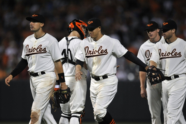 Aug 8, 2014; Baltimore, MD, USA; Baltimore Orioles teammates celebrate after their game against the St. Louis Cardinals at Oriole Park at Camden Yards. The Orioles won 12-2. Mandatory Credit: Joy R. Absalon-USA TODAY Sports
