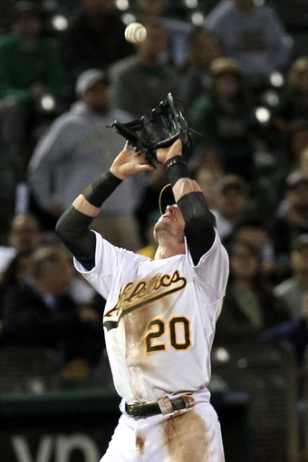 Aug 8, 2014; Oakland, CA, USA; Oakland Athletics third baseman Josh Donaldson (20) catches Minnesota Twins second baseman Brian Dozier (2) fly ball in the eighth inning at O.co Coliseum. Mandatory Credit: Lance Iversen-USA TODAY Sports.