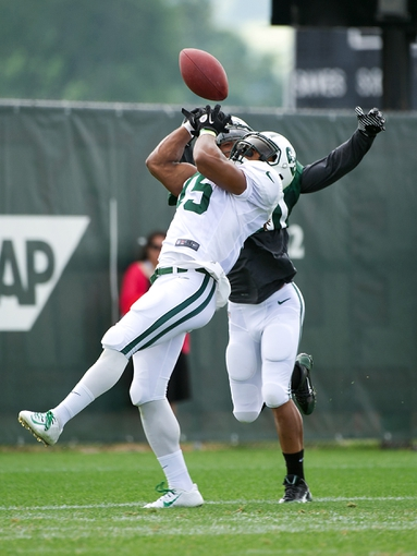 Aug 4, 2014; Cortland, NY, USA; New York Jets wide receiver Saalim Hakim (15) attempts to make a catch in front of cornerback Kyle Wilson (20) during training camp at SUNY Cortland. Mandatory Credit: Rich Barnes-USA TODAY Sports