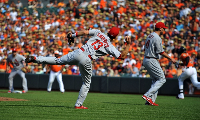Aug 9, 2014; Baltimore, MD, USA; St. Louis Cardinals third baseman Matt Carpenter (13) throws over to first base but can't get out Baltimore Orioles third baseman Manny Machado (not shown) in the first inning at Oriole Park at Camden Yards. Mandatory Credit: Joy R. Absalon-USA TODAY Sports