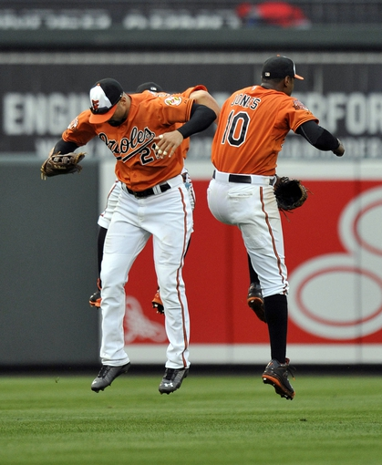 Aug 9, 2014; Baltimore, MD, USA; Baltimore Orioles outfielders David Lough (rear) Nick Markakis (center) and Adam Jones (right) celebrate after a game against the St. Louis Cardinals at Oriole Park at Camden Yards. The Orioles defeated the Cardinals 10-3. Mandatory Credit: Joy R. Absalon-USA TODAY Sports