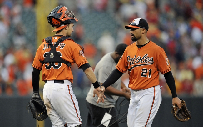 Aug 9, 2014; Baltimore, MD, USA; Baltimore Orioles catcher Caleb Joseph (36) congratulates Nick Markakis (21) after a game against the St. Louis Cardinals at Oriole Park at Camden Yards. The Orioles defeated the Cardinals 10-3. Mandatory Credit: Joy R. Absalon-USA TODAY Sports