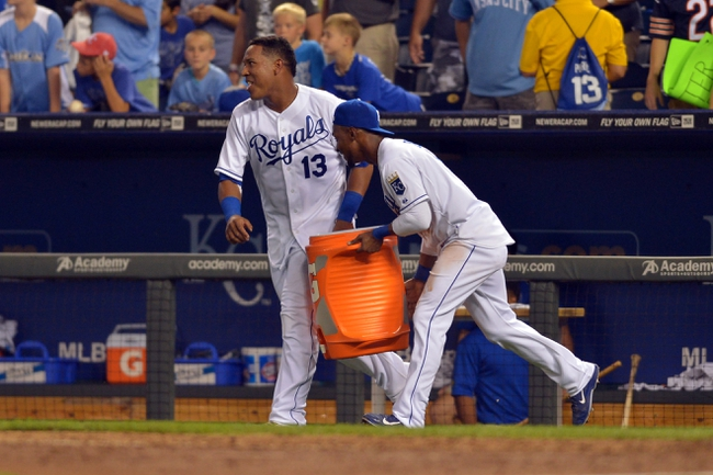 Aug 9, 2014; Kansas City, MO, USA; Kansas City Royals catcher Salvador Perez (13) and center fielder Jarrod Dyson (1) prepare to dump a cooler on starting pitcher James Shields (not pictured) after the game against the San Francisco Giants at Kauffman Stadium. The Royals won 5-0. Mandatory Credit: Denny Medley-USA TODAY Sports