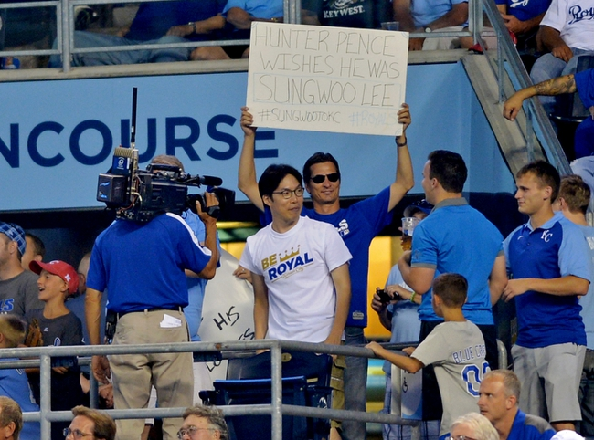 Aug 9, 2014; Kansas City, MO, USA; A Kansas City Royals fan holds a San Francisco Giants right fielder Hunter Pence (8) sign above Sung Woo Lee, the fan visiting from Korea during the seventh inning against the San Francisco Giants at Kauffman Stadium. The Royals won 5-0. Mandatory Credit: Denny Medley-USA TODAY Sports