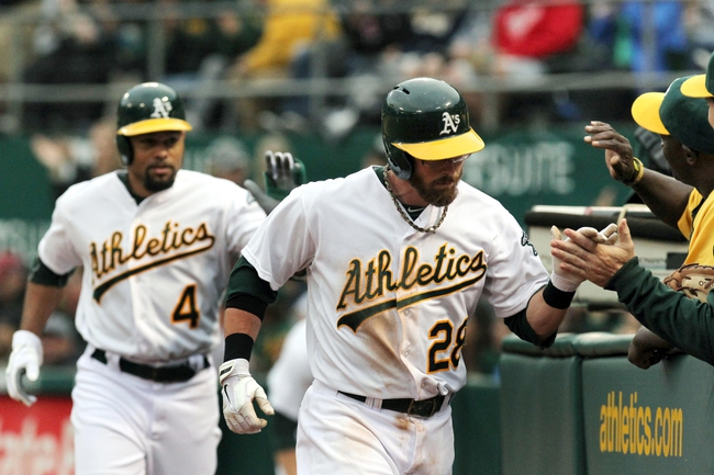 Aug 9, 2014; Oakland, CA, USA; Oakland Athletics second baseman Eric Sogard (28) and Coco Crisp (4) are greeted at the dugout after they scored on a two run RBI single by third baseman Josh Donaldson (not pictured) in the second inning of their MLB baseball game with the Minnesota at O.co Coliseum. Mandatory Credit: Lance Iversen-USA TODAY Sports