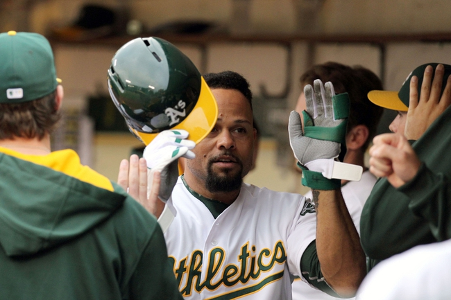 Aug 9, 2014; Oakland, CA, USA; Oakland Athletics center fielder Coco Crisp (4) is greeted in the dugout after scoring on a two run RBI single by third baseman Josh Donaldson (not pictured) in the second inning of their MLB baseball game with the Minnesota at O.co Coliseum. Mandatory Credit: Lance Iversen-USA TODAY Sports