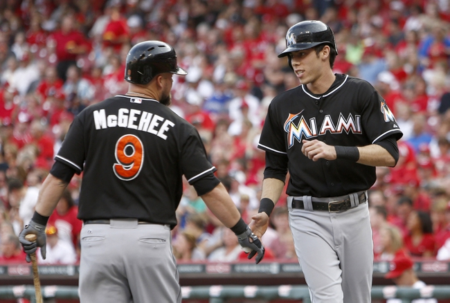 Aug 9, 2014; Cincinnati, OH, USA; Miami Marlins left fielder Christian Yelich (right) is congratulated by third baseman Casey McGehee (9) after Yelich scored on a sacrifice fly by Giancarlo Stanton (not pictured) in the first inning against the Cincinnati Reds at Great American Ball Park. Mandatory Credit: David Kohl-USA TODAY Sports
