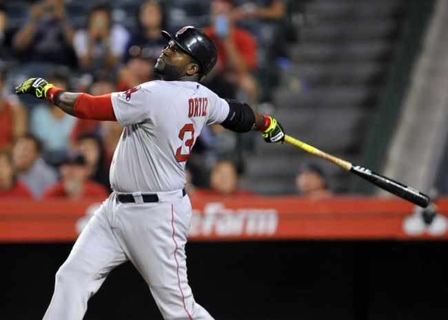 August 9, 2014; Anaheim, CA, USA; Boston Red Sox designated hitter David Ortiz (34) hits a sacrifice RBI in the fourteenth inning against the Los Angeles Angels at Angel Stadium of Anaheim. Mandatory Credit: Gary A. Vasquez-USA TODAY Sports