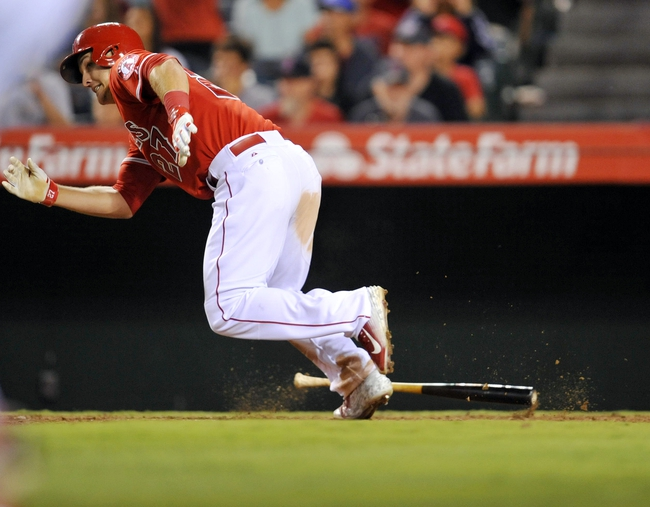 August 9, 2014; Anaheim, CA, USA; Los Angeles Angels designated hitter Mike Trout (27) hits an RBI single in the fourteenth inning against the Boston Red Sox at Angel Stadium of Anaheim. Mandatory Credit: Gary A. Vasquez-USA TODAY Sports
