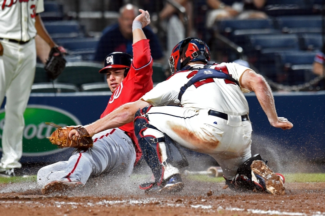 Aug 9, 2014; Atlanta, GA, USA; Washington Nationals catcher Wilson Ramos (40) is tagged out on a play at home plate by Atlanta Braves catcher Evan Gattis (24) during the eleventh inning at Turner Field. The Nationals defeated the Braves 4-1 in eleven innings. Mandatory Credit: Dale Zanine-USA TODAY Sports