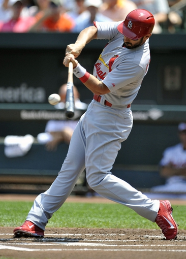 Aug 10, 2014; Baltimore, MD, USA; St. Louis Cardinals designated hitter Matt Carpenter (13) singles in the first inning against the Baltimore Orioles at Oriole Park at Camden Yards. Mandatory Credit: Joy R. Absalon-USA TODAY Sports