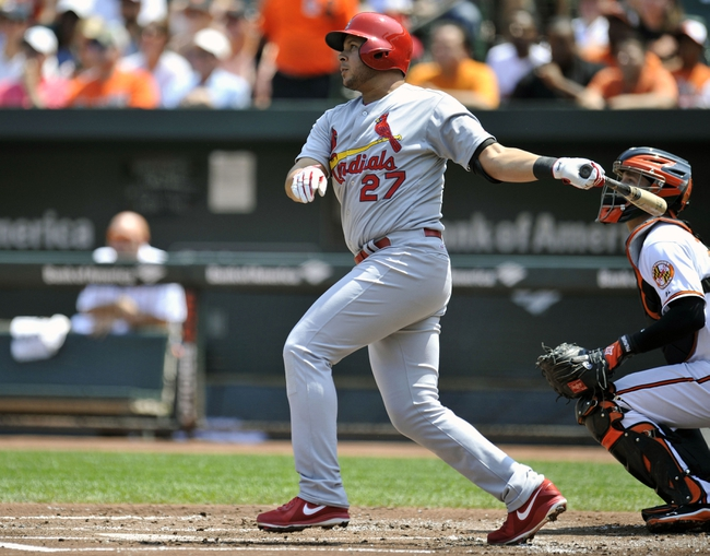 Aug 10, 2014; Baltimore, MD, USA; St. Louis Cardinals shortstop Jhonny Peralta (27) hits a one-run rbi single in the first inning against the Baltimore Orioles at Oriole Park at Camden Yards. Mandatory Credit: Joy R. Absalon-USA TODAY Sports