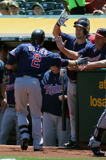 Aug 10, 2014; Oakland, CA, USA; Minnesota Twins second baseman Brian Dozier (2) is greeted at the dugout after hitting a solo home run against the Oakland Athletics in the first inning of their MLB baseball game at O.co Coliseum. Mandatory Credit: Lance Iversen-USA TODAY Sports