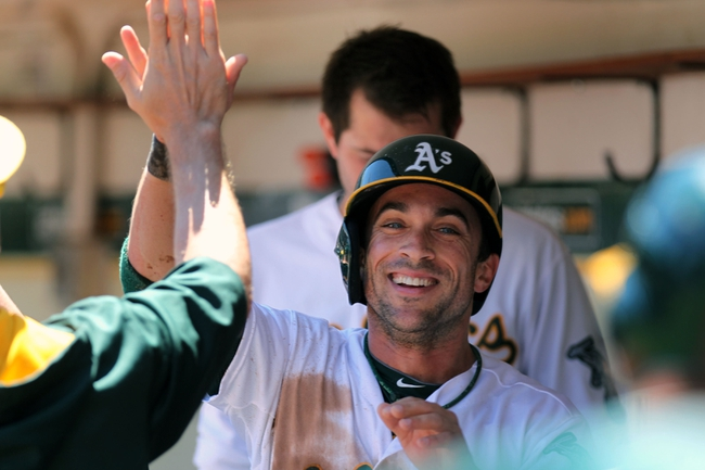 Aug 10, 2014; Oakland, CA, USA; Oakland Athletics center fielder Sam Fuld (23) is greeted in the dugout after scoring off a RBI single by first baseman Stephen Vogt (37) (not pictured in the first inning of their MLB baseball game with the Minnesota Twins at O.co Coliseum. Mandatory Credit: Lance Iversen-USA TODAY Sports