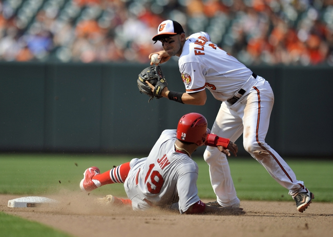 Aug 10, 2014; Baltimore, MD, USA; St. Louis Cardinals center fielder Jon Jay (19) is out at second base but Baltimore Orioles shortstop Ryan Flaherty (3) cannot complete the double play in the seventh inning at Oriole Park at Camden Yards. The Cardinals defeated the Orioles 8-3. Mandatory Credit: Joy R. Absalon-USA TODAY Sports