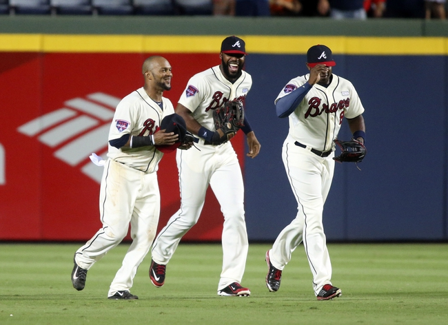 Aug 10, 2014; Atlanta, GA, USA; Atlanta Braves center fielder Emilio Bonifacio (1, left), right fielder Jason Heyward (22) and left fielder Justin Upton (8) celebrate after their win over the Washington Nationals at Turner Field. The Braves won 3-1. Mandatory Credit: Jason Getz-USA TODAY Sports