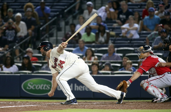 Aug 10, 2014; Atlanta, GA, USA; Atlanta Braves catcher Evan Gattis (24) hits an RBI single scoring third baseman Chris Johnson (not pictured) as Washington Nationals catcher Wilson Ramos (40) is shown on the play in the eighth inning of their game at Turner Field. The Braves won 3-1. Mandatory Credit: Jason Getz-USA TODAY Sports