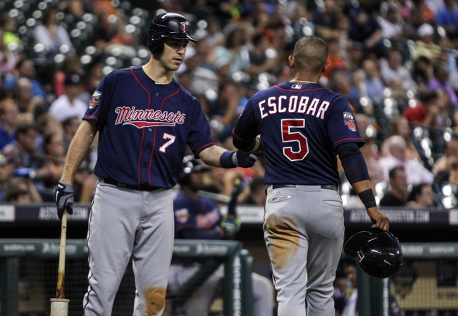 Aug 11, 2014; Houston, TX, USA; Minnesota Twins shortstop Eduardo Escobar (5) is congratulated by first baseman Joe Mauer (7) after scoring a run during the fourth inning against the Houston Astros at Minute Maid Park. Mandatory Credit: Troy Taormina-USA TODAY Sports